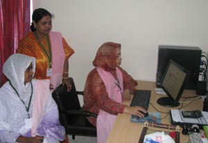 Three Bangladeshi women gather around a desktop computer, one seated using the mouse and keyboard, others behind her