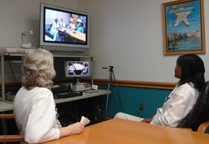 Two women seated at conference table, looking at teleconferencing equipment, with a screen that shows another conference room