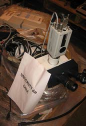 Close up of pile of scientific equipment and wires partially covered with clear plastic wrapping