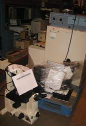 Large piles of scientific equipment including large microscopes and large metal box shapes, wrapped partially in clear plastic