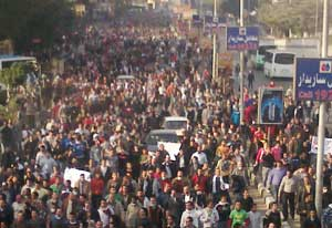 Crowded street in Egypt packed with protesters walking, some abandoned cars in road, some carry signs