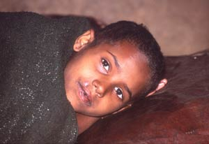 Young Ethiopian child rests on its side, wrapped in a blanket, looks into camera
