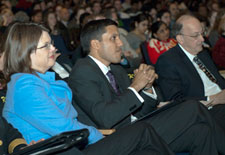 Dr. Rajiv Shah sits in audience seated between Dr. Roger Glass and Lois Quam, full audience in background