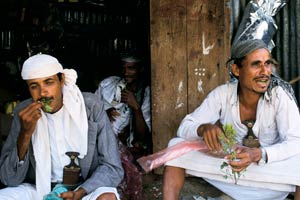 Two men sit in front of wooden hut, one with droopy eyes stuffs handful of khat into his mouth, the other looks off the camera