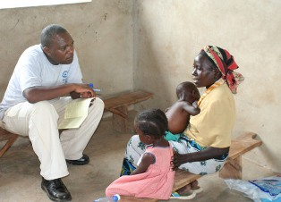A man counsels a woman (with her two young children) about nutrition in Kenya.