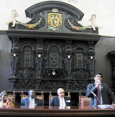 Dr. N. Kumarasamy speaks to audience at the historic Palacio de la Autonomia with other panelists: Dr. Danstan Begenda,