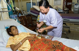 A nurse delivers medication to a patient at a Cambodian hospital. Photo credit: David Snyder