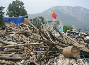a picture of destroyed buildings in China with Chinese flag sticking out of the rubble. Photo by Ma Hong.