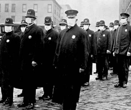 a black and white photo of Seattle police wearing flu masks standing shoulder to shoulder, during the 1918-1919 pandemic.