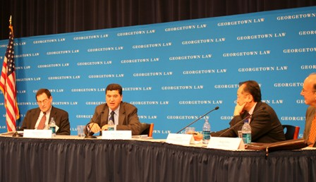 Four panelists address issues, a blue Georgetown Law backdrop in white letters and American flag is seen on the left.