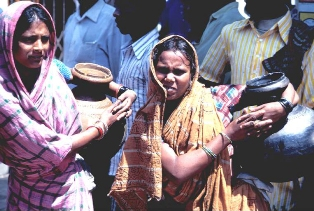 Two Indian women standing in a line holding large water jugs under their arms.