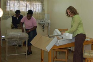 Krista Pfaendler and her Zambian colleagues opening boxes of new lab equipment.