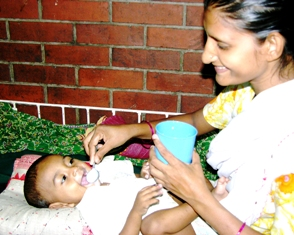 A Bangladeshi woman giving her baby a spoonful of a solution of water, salt and sugar. Photo: ICDDR, B