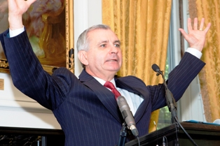 Sen. Jack Reed, D-R.I., with arms open wide, describes Fogarty's influence to the audience.