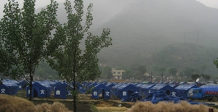 a photo of a refugee camp. Hundreds of blue tents are set up in a field with misty mountains behind them. Photo by Ma Hong.