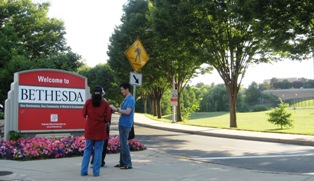 Three Fogarty scholars standing in front of the Welcome to Bethesda sign near the NIH campus. Part of the campus can be seen off to the right side.