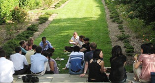 Fogarty scholars sitting down on the stairs and grounds of the Stone House gardens at their BBQ.