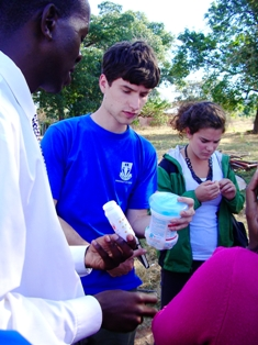 Local students with the headmaster of a school in South Africa examining a water purification system he set up. Photo credit: J. Boissevain