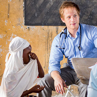 Dr Cameron Gaskill with stethoscope around his neck sitting next to a child