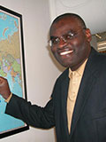 Dr. Clement Adebamowo looks at camera, smiling, points to map