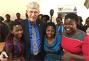 NIH Director Francis Collins poses for the camera with three young women in Uganda