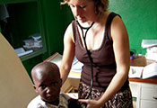 Dr Manning in an exam room with stethoscope in ears holds it to a young boy's back, she looks down at him