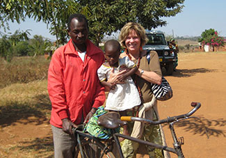 Peggy Bentley holds a young child, stands next to a man who balances a bicycle on a dusty road in Malawi