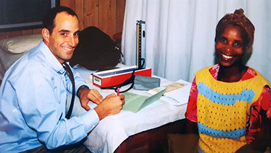 Dr. Thomas Gaziano seated in exam room and taking notes next to smiling female patient