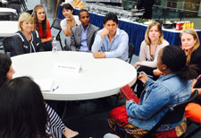 Dr. Denise Russo of NICHD speaks with fellows and scholars during 2015 orientation while seated around a table