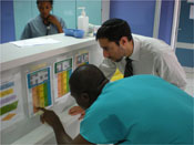 Two male medical staff lean toward counter to read charts and schedules of patients in hospital