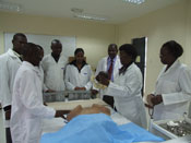 Group of medical students in white lab coats stands around hospital bed, woman leading discussion points to model she holds