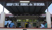 Hospital entrance, people gathered outside waiting, sign overhead reads Hospital Rural de Mocuba