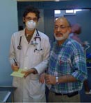 In hospital hallway a young male doctor in white coat wearing surgical mask stands next to older man in plaid shirt