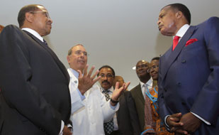 NIH clinical center Dir Gallin wearing white coat gestures with hands while giving tour to African presidents, delegates