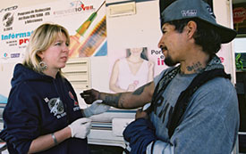 Woman wearing plastic gloves holds the arm of a man in front of a mobile health clinic