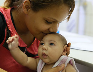 Photo by Harold Ruiz/PAHO-WHO, in Brazil, a mother kisses baby, who has a smaller than usual head