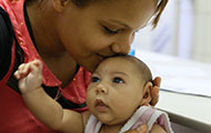 In Brazil, a mother kisses baby, who has a smaller than usual head
