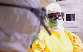 Photo by Cleopatra Adedeji/CDC. Inside CDC's mock Ebola treatment unit, two trainees review each other's use of personal protective equipment.