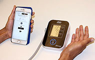 Close up of hands using blood pressure monitor next to a smartphone