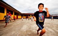 Children happily run and play outside in a school courtyard