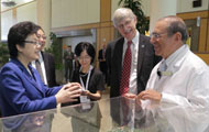 Chinese delegation gathers around architectural model in lobby of clinical center with Dr Francis Collins and Dr John Gallin