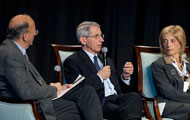 NIAID Dir Fauci speaks on stage, Fogarty Dir Glass and NHLBI Dir Shurin look on