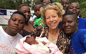 Dr. Diana Bianchi, center holding a baby, surrounded by young people in Kenya.