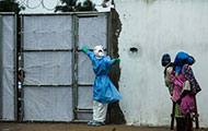 Photo by Morgana Wingard, courtesy of USAID, Healthcare worker outside Ebola clinic in full protective gear holds gate closed, w
