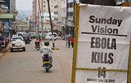 Photo by CDC/CC BY 2.0. Headline of newspaper reads 'Ebola kills 14' on busy street in Kampala, Uganda, highlights nationwide concern of the outbreak.