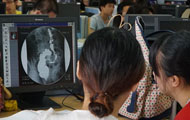 Two women with backs to camera review a medical image on a monitor in a crowded computer lab