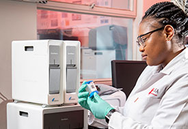 Photo courtesy of CAPRISA. Female researcher working wearing lab coat and gloves examines testing supplies in front of lab equipment in a CAPRISA lab.