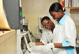 Two female researchers review documents and data together in a lab