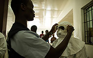 Photo by Morgana Wingard for USAID: Healthcare workers put on personal protective equipment in Liberia
