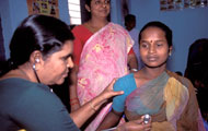 Indian woman seated in health clinic, female health care worker uses stethoscope to listen to chest